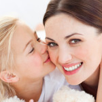 Close-up of a blond little girl kissing her mother