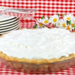 One whole whipped cream pie on a red and white tablecloth with flowers and plates in the background.  Could be any type of cream pie.