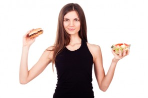 A woman stands on a white background, holding a burger and a salad