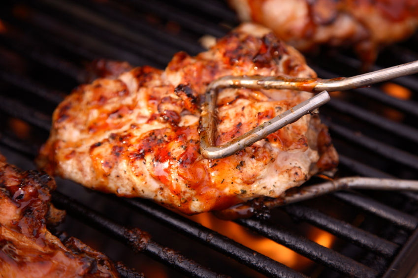 turning barbeque chicken on the grill with tongs